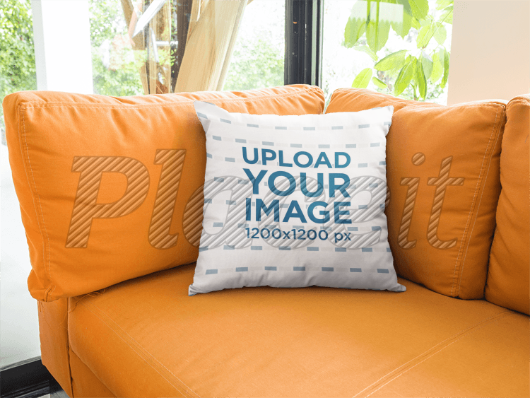 placeit square pillow template lying on an orange sofa in a living