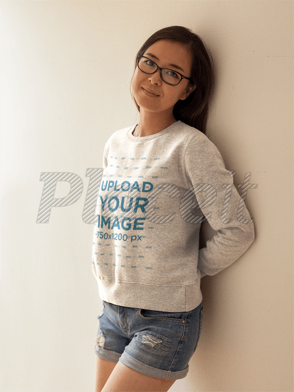 b0f3ad432c04 Cute Girl with Glasses Wearing a Crewneck Sweatshirt Template While Lying  Against a White Wall