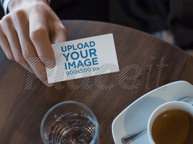 placeit man showing a business card template while at the cafe